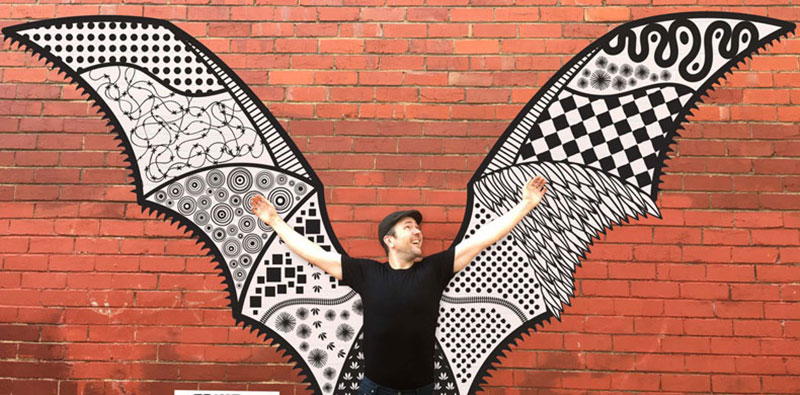 Man standing infront of wing art work on wall