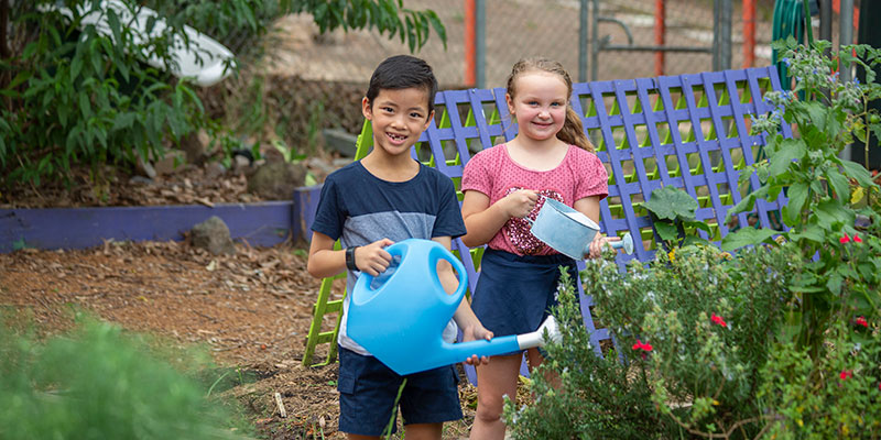two kids using watering cans