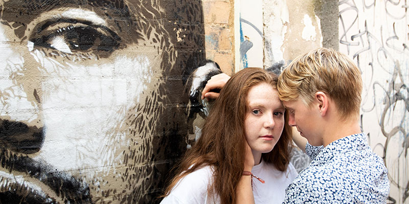teenage boy and girl standing against wall